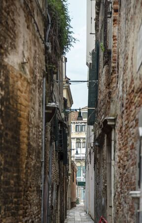 View of a typical Venetian narrow street with brick old houses