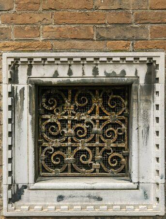 Old rusty wrought-iron lattice on a brick wall in venice Archivio Fotografico
