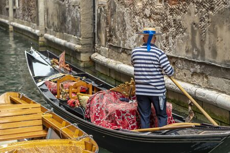Gondolier in a stripped vest floating on a gondola through a narrow channel in Venice