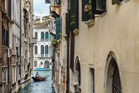 Gondolier in a stripped vest floating on a gondola through a narrow channel among the cozy italian houses in Venice Archivio Fotografico