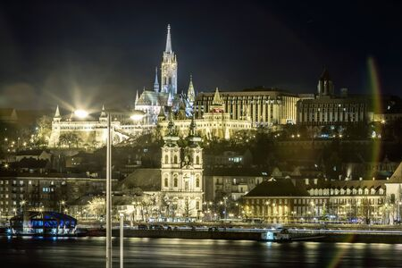 Night view of St. Matthias Church from the east side of Danube with motor ships on it