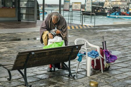 VENICE, ITALY - 25 August, 2018: Homeless man gets something out of the bag on a bench in the street of Venice Archivio Fotografico - 137706424