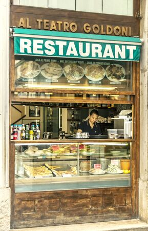 VENICE, ITALY - 25 August, 2018: Fast food restaurant showcase with a waiter who prepares food inside Redakční