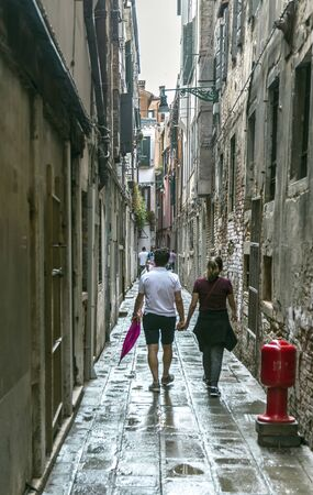 Romantic couple walking holding hands at the narrow historical street in Venice Archivio Fotografico