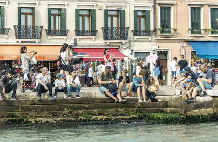 VENICE, ITALY - 25 August, 2018: Tourists sitting, relaxing and taking pictures on the canal in Venice 新聞圖片