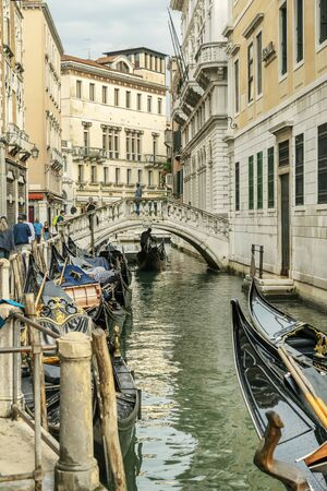 VENICE, ITALY - 25 August, 2018: Old canal with boats and bridge in Venice, Italy. Street with old Italian architecture of Venice Archivio Fotografico - 137706433