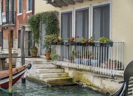 VENICE, ITALY - 25 August, 2018: Porch of Italian house with a lot of flower pots and with boat near the house