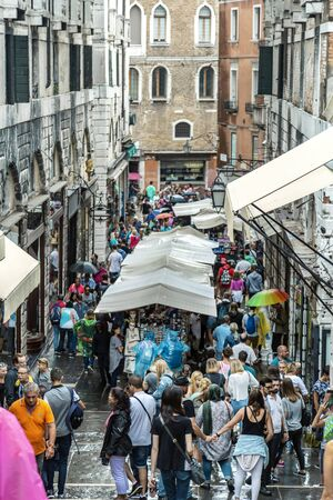 VENICE, ITALY - 25 August, 2018: Lively Venetian street with many tourists