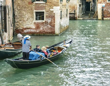 VENICE, ITALY - 25 August, 2018: Gondolier in a stripped vest floating with people on a gondola through a narrow channel in Venice