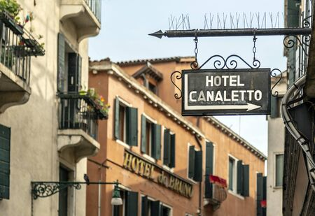 VENICE, ITALY - 25 August, 2018: Croped frame overlooking the Italian street and the sign of the hotel Redactioneel