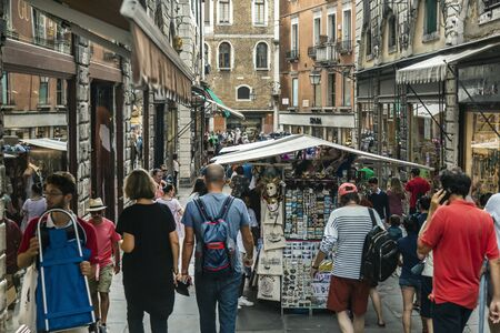 VENICE, ITALY - 25 August, 2018: View of the lively Italian street with tourists and souvenir shops