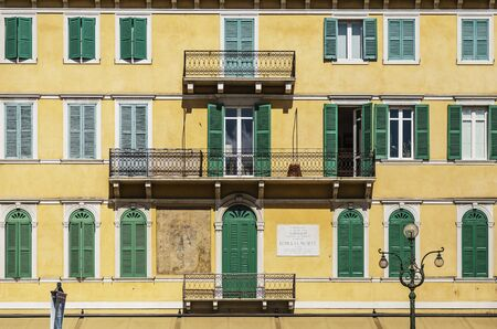VERONA, ITALY - AUGUST 26, 2018: Symmetrical view on a typical picturesque fasad of house in Verona, with colored shutters on the windows and forged balconies Redakční