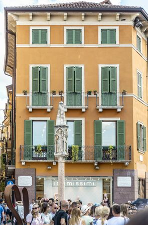 VERONA, ITALY - AUGUST 26, 2018: Fasad of picturesque orange building with green shutters on the windows