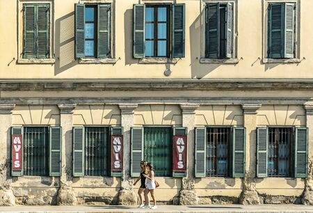 VERONA, ITALY - AUGUST 26, 2018: Symmetrical view on a fasad of house in Verona, people walking on the street Editoriali