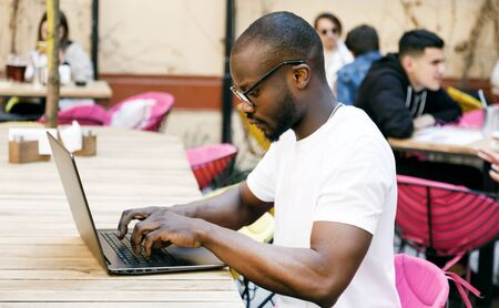 African smart student browsing something at the Internet with the laptop while sitting at the cafe