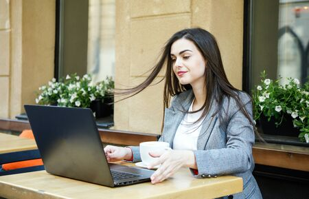 Young sucsessful business woman started working with laptop after coffee break at the street cafeteria