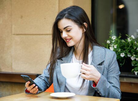 Young business woman using smartphone while drinking coffee at the street cafeteria