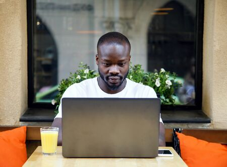 African handsome student working with laptop at the outdoor cafe