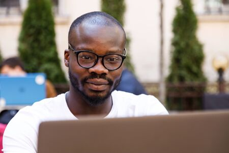 Portrait of african smart student wearing glasses using laptop while sitting at the cafe