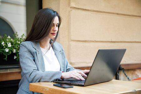Young attractive business woman sitting outdoors with laptop