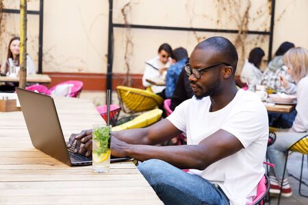 African smart student wearing glasses studying with laptop and drinking mohito at the cafe