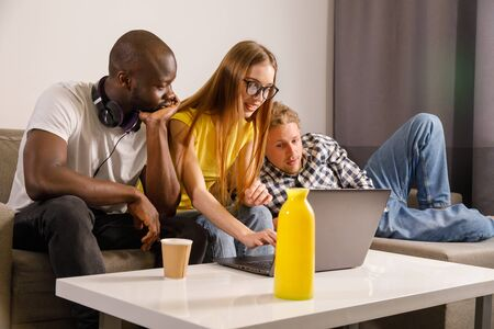 Diverse students with laptop in home interior looking at the computer