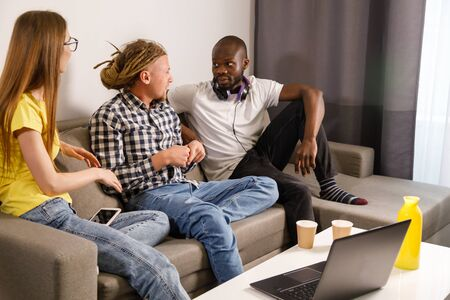 Multicultural smiling friends sitting on couch and chatting with each other