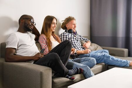 A group of friends are having fun watching TV in the room