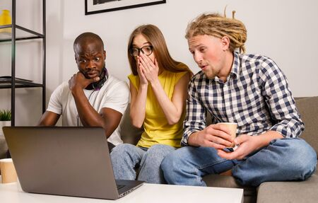 Schocked group of friends watching intresting scary movie on laptop