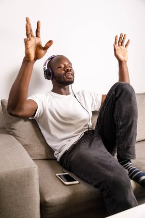 Young african man relaxing with headphones, listening music with eyes closed and gesticulating