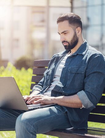 Handsome young man using laptop in city on a summer day Stockfoto