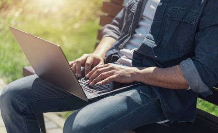 Close up view of multicultural businessman siting on a bench and working with his laptop Stockfoto