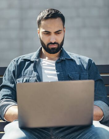 Young handsome businessman sitting on a wooden bench in the city with a laptop