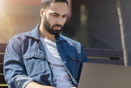 Portrait of handsome cheerful business man sitting on bench outside and working on laptop
