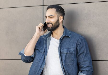 Happy young businessman calling with mobile phone on the street Stockfoto