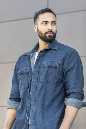 Portrait of bearded confident multicultural man in jeans shirt standing near the modern building