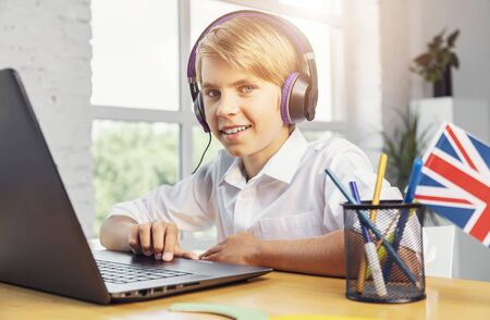 Smiling boy at the laptop enjoys learning English online
