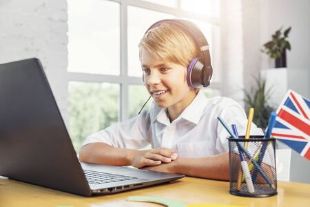Enthusiastic kid in headphones studying English online