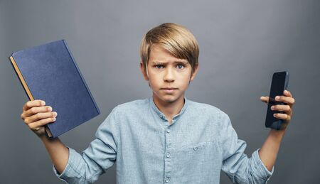 Blond Boy is in doubt choosing between book and smartphone