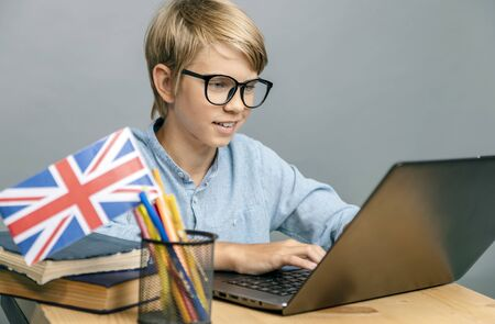 Enthusiastic pupil in glasses studying English by the laptop