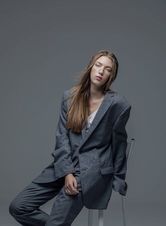 Portrait of weary young beautiful woman in oversized mans suit sitting isolated grey background Stock Photo