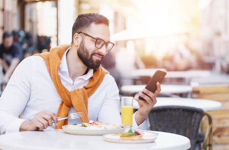 Bearded multicultural businessman in white shirt having phone conversation at the cafe