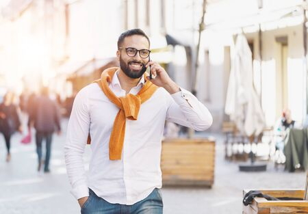 Bearded multicultural businessman walking on the street while speaking on the smartphone