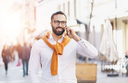 Bearded multicultural businessman walking on the street and using smartphone