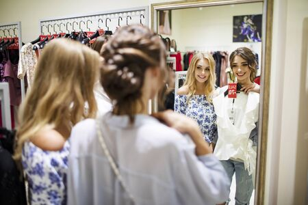 Smiling shopping girlfriends trying white blouse in front of a mirror Banco de Imagens