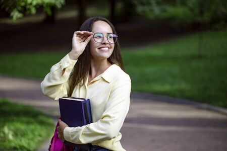 Portrait of cute cheerful student girl adjusting glasses on a campus park path Stockfoto