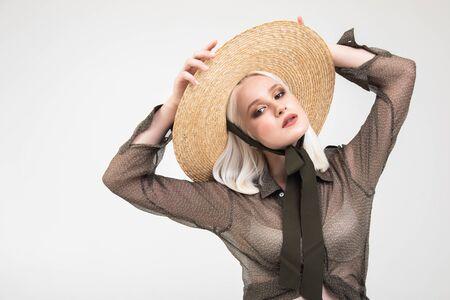 Retrato de atractiva chica rubia platino en blusa negra transparente ajustando el sombrero de paja aislado fondo blanco.