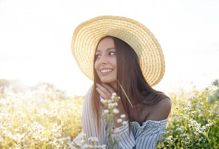 Charming brown-haired girl in straw hat and white dress enjoys sitting on the flowery meadow