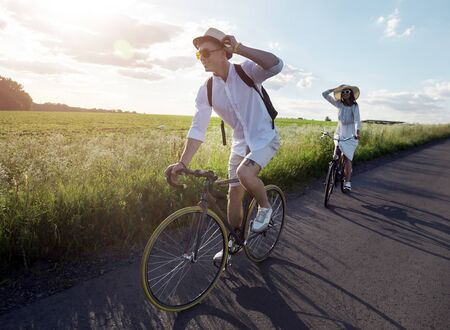 Young couple has a bicycle trip at summer countryside