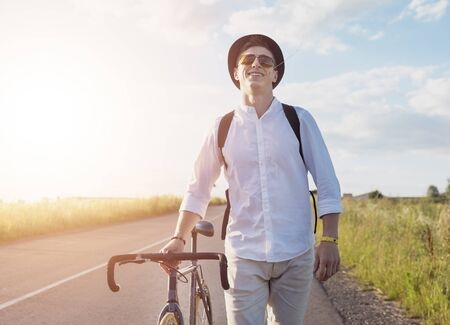 Young male cyclist walking by feet with a grass stalk in his mouth on a sunset background Stockfoto
